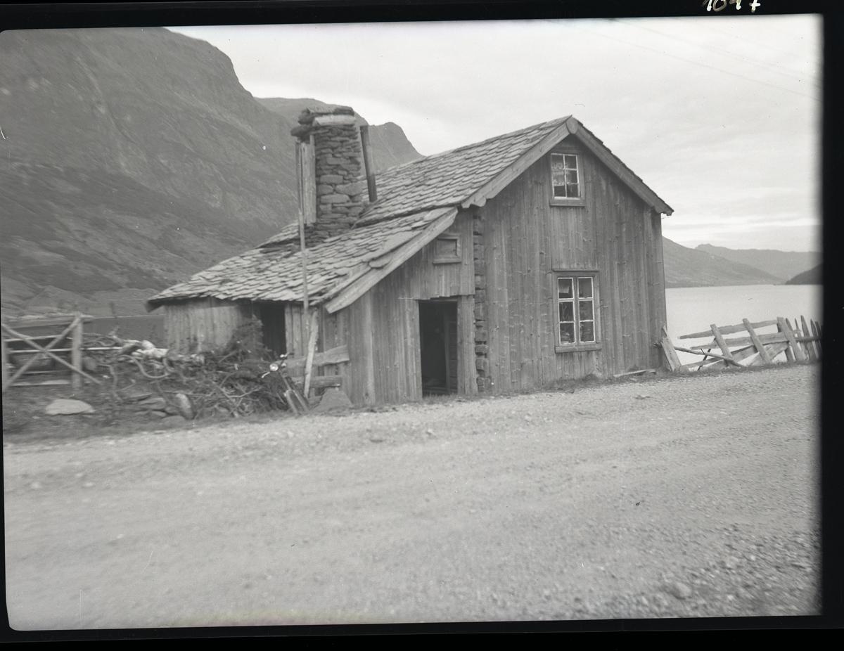 Motiv av eldre hus som står ved veikanten. Vangsmjøsa i bakgrunnen.