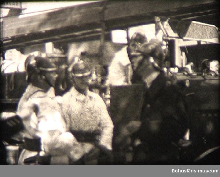 """1)Film om Uddevalla brandkår. 0012 Utryckning ur Uddevalla gamla brandstation. 0025 Gamla brandbilarna från 1920-talet nr.  2 och 3 rycker ut;  bilarna försedda med massiva däck. 0028 Ambulansbilen, Volvo från 1930-talet,  rycker ut. 0029 Bilarna kör norrut över Torggatan;  i bakgrunden huset med tidn.  """"Bohus-Postens"""" lokaler i korsningen  Torggatan-Lagerbergsgatan. 0034 Kilbäcksgatan österut.  Bilarna kör runt Margretegärc parken som ligger t.v.  I bakgrunden ligger kv. Hernhut med gamla tändsticksfabrikens lokaler.  2)Eldsvådan på Södra Drottninggatan-Sörkällan. 0043 Branden vid Södra Drottninggatan 36. 0047 Södra Drottninggatan norrut. 0053 T.h.  Brandchefen Eric Ström och t.v. polismannen Mikael Svanberg. 0059 Eldhärjade fastighetens fasad mot gårdssidan. Vindsbrand med vattenskador i våningarna under. 0104 Kiosken i Sörkälleparkens östra del samt järnvägsporten mot Kapellevägen (kallades för """"Kör Sakta""""    efter en varningsskylt på andra sidan). 0105 Vice brandchefen Martin Kjellén. 0115 Förre vice brandchefen P.A. Pettersson, tillika ingeniör vid Uddevalla Tändsticksfabrik, samt brandman Holger Dahlström t.v.  3)        0126 Invigning av polis- och brandtelegrafen. Fr.v.  i dörren Gustav Lindblom, stadsfiskal Emil Håkansson och nr. två från höger borgmästare Hugo Westin. 0130 I mitten med ulster,  drätseldirektör Nils Elmer. 0133 I dörren stadsingeniör Oskar Kornell (med käpp) Längst  t.h. (med kubb) bankdir.  Georg Karlsson.  4)       Uppvisning vid Walkesborg. På fasaden vid huset Walkesborg (Södra Hamngatan 3) finns en av de nya brandtelegraferna uppmonterad. 0134 Inför invigningen av telegrafen och brandkårens kommande uppvisning """"slås larm"""" av vice konsuln och direktören Herman Sanne. 0142 Larmcentralen på brandstationen tager emot larmet. 0223 Brandkårens uppvisning vid Walkesborg pågår med evakuerings trummor,  brandsegel och motorsprutor. 0312 Även den gamla ångdrivna sprutan visades, trots att den ersatts med motordrivna sprutor. 317 Brandbil nr.  1,"""