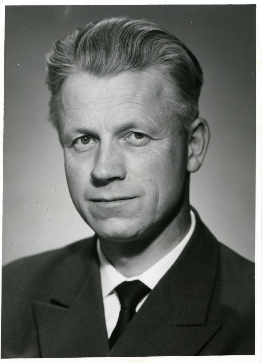 Portrett av en mann. Mannen er iført mørk dress med hvit skjorte og slips.
