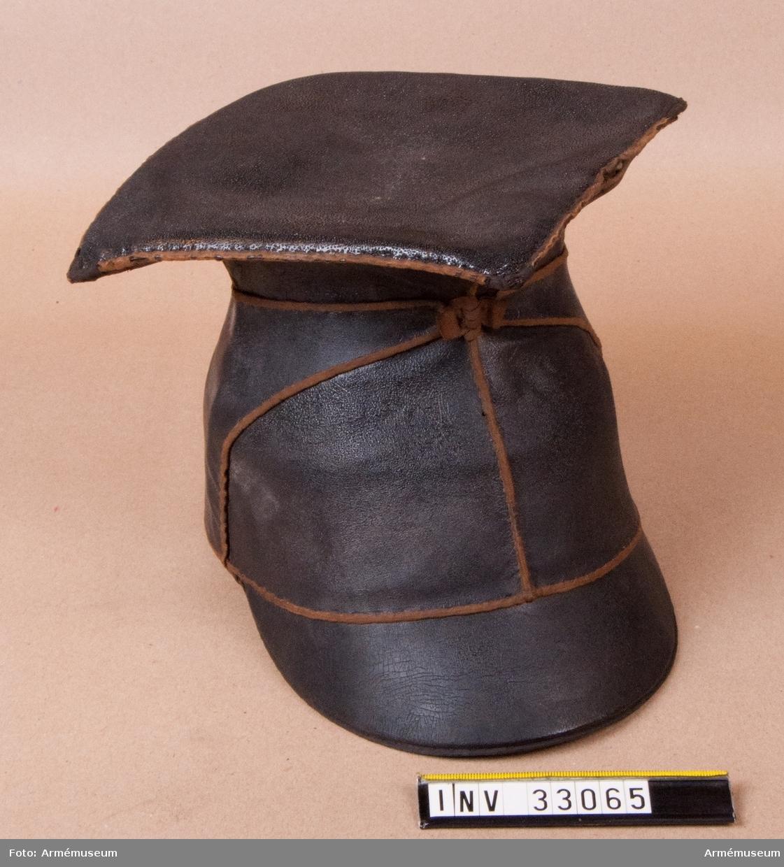 Grupp C I. Överklädd lansiärmössa för Livgardet till häst. Av 1852 års förändrade modell för officer. Se Generalmönsterrulla 1879. Pris kronor 50:- vid inköpet 1959.