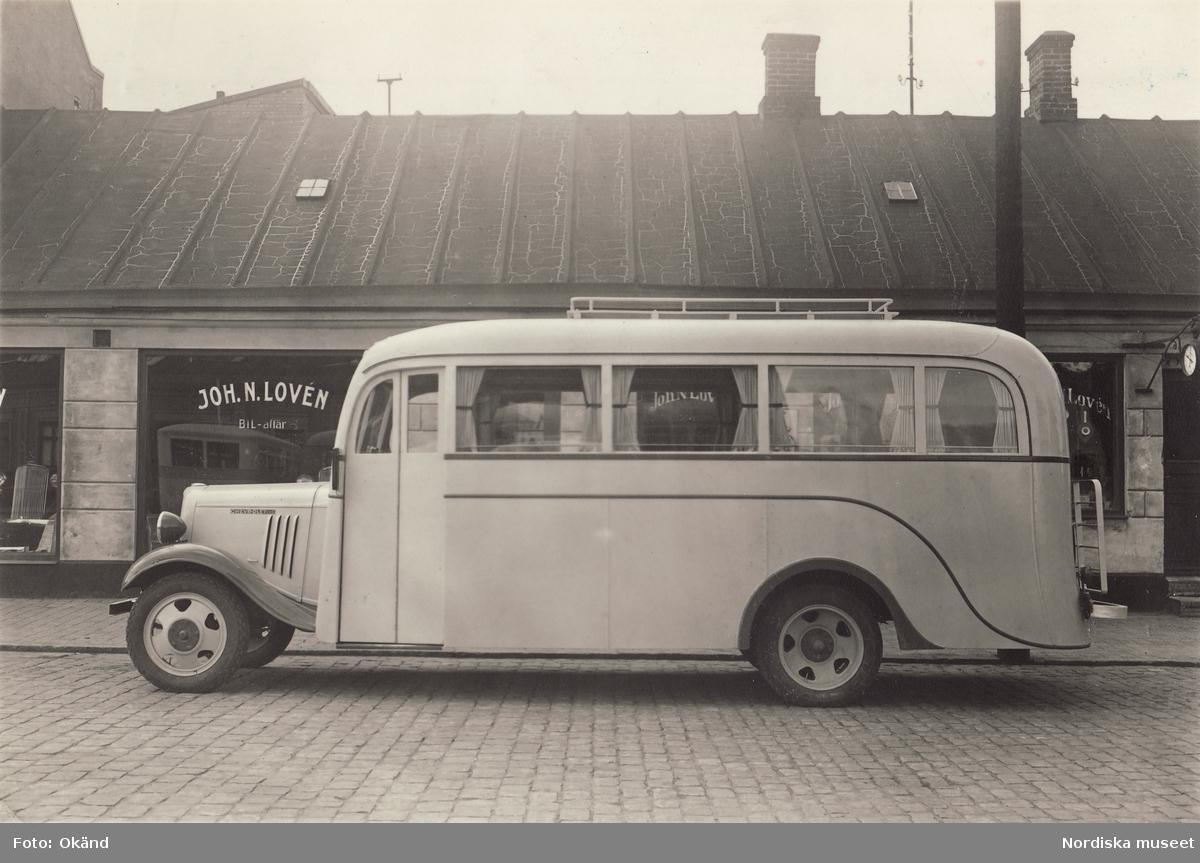 """""""En ny Chevrolet 157 D.H.S.buss utanför Joh. N. Lovéns Bilaffär i Tomelilla (Tel. 71). Bussen skall levereras till Vitemölla Omnibuss, strax utanför Kivik i Skåne. Baksidestext: Bussen väger 3080 kg, föraren 80 kg, tillsammans 3160 kg, 22 personer á 80 kg = 1760 kg, Paket gods 80 kg = 1840 kg. Tillsammans 5000 kg. Omnibussen är byggd för 23 personer utom föraren."""""""