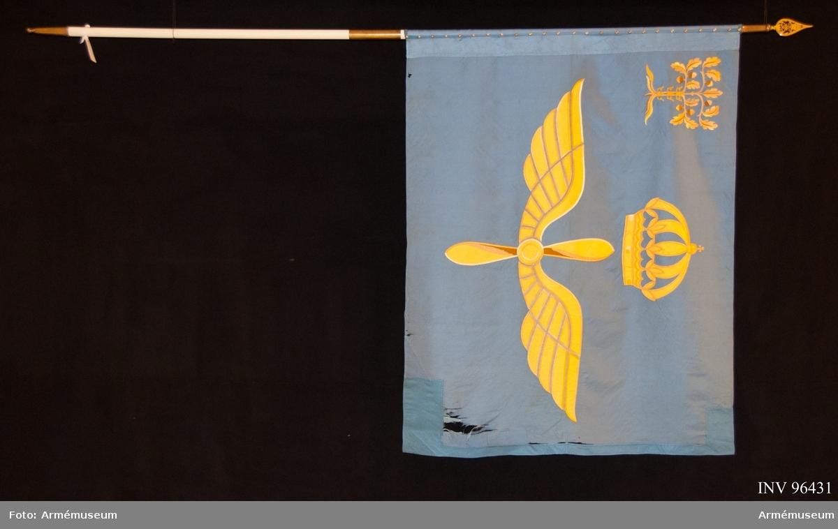 Duk av ljusblått kypertvävt siden. Motiv utfört i intarsia och läggsöm. Handbroderad. Föreställande en vingad, tvåbladig propeller under en kunglig krona, allt i gult. I övre inre hörnet landskapet Blekinges vapenbild; en ek med tre kronor uppträdda på stammen, allt i gult. Duken lagad både vid stångsidan och flygsidan.  Delbar stång. På doppskon ingraverat: KUNGL BLEKINGE FLYGFLOTTILJ.  Spets med Gustav V:s monogram.  KT 2011-10-27