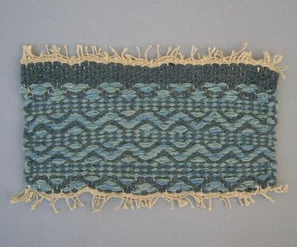 Mattprov i rosengång.Linnemattvarp med inslag av nöthårsgarn i olika blå nyanser. Mönstret är komponerat av Anna Hådell.