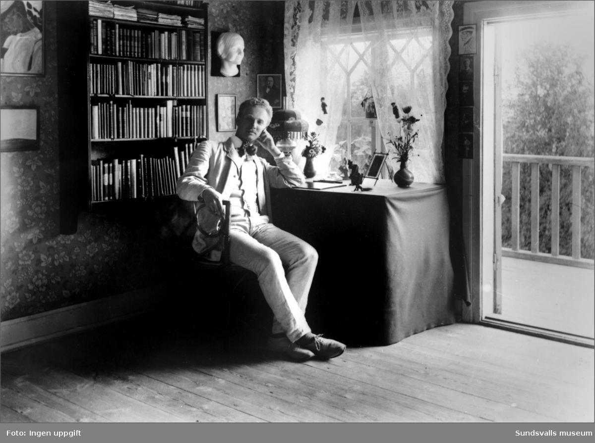 """Ture Nerman, författare, journalist och politiker. Han arbetade först som journalist och senare som chefredaktör på Nya Samhället. Under sin period i Sundsvall bodde han ett par år på Sallyhills gård, där denna bild är hämtad. I sina memoarer """"Allt var rött"""" skriver han om denna tid. """"I slutet av september flyttade Englund och jag in två rum på övre botten i ett gammalt träslott, Sallyhill, bortöver Sidsjövägen, en idyll övervuxen av humle och klängblommor, i en tät igengrodd gammal park. Det stora rummet tvärsöver huset med veranda åt Selångersdalen tog jag, Englund sidorummet med oregelbundet tak, tre fönsternischer och grön dager av lindar och syrener utanför. Vår värdinna var änkefru Linderberg, en rar gammal dam ur en artonhundratalsroman.""""  Det stora rummet blev ett underbart arbetsrum, som jag dessutom kunde möblera själv i egen smak, egentligen med en enda möbel men central: ett skrivbord i allmogestil med korslagda ben, snickrat av gamle snickare Kärnlund nere i gårdsflygeln. Över bordet la jag en grön bojduk i det historiska dramats stil och på bordet satte jag lampa, blomstervas, vykortsfotot av den ameri-kanska skönhetsdrottningen Marguerite Frey och en liten djävul av järn, en figur från ett tändstickställ, som räckte lång näsa trevligt oppkäftigt och som jag hade hittat i en lumpbod i Stockholm. Det var ett bord! Där skulle man kunna skriva ett trosdrama…"""""""