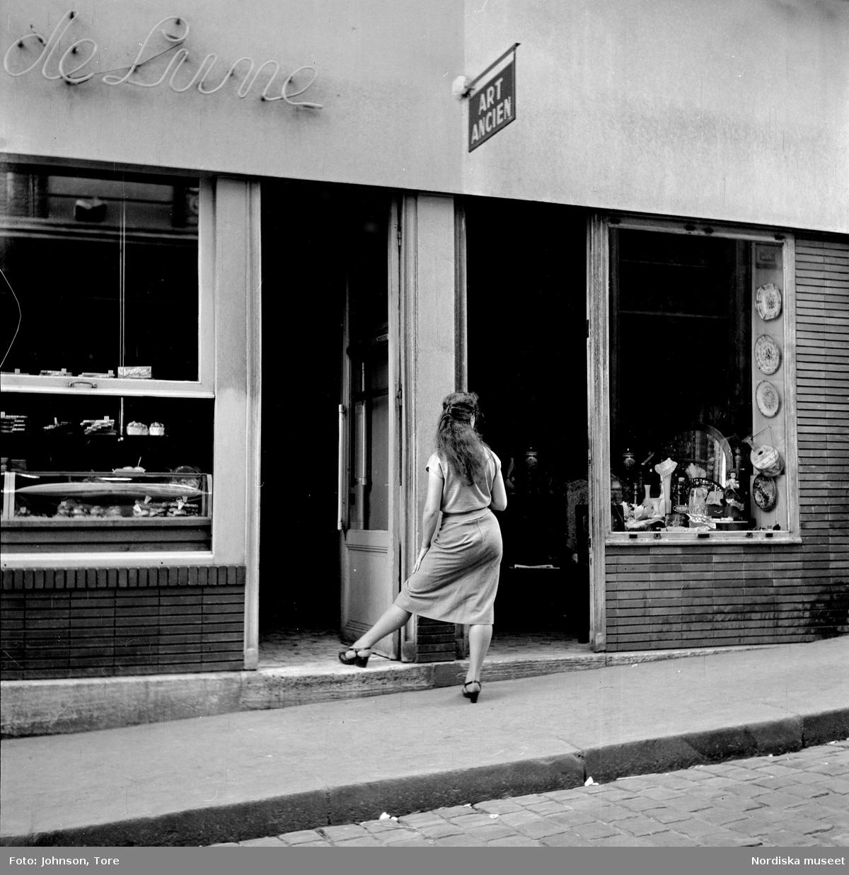 Paris. Kvinna i dörren till antikvitetsaffär.