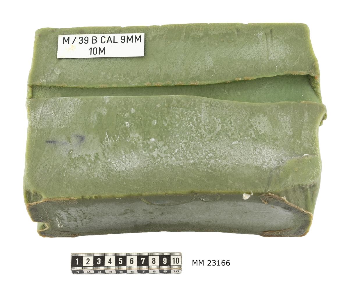 """Grönt hårt rektangulärt tvålblock. Påklistrad vit plastbricka på blockets ovansida med information om vapensort, caliber och avstånd angivet i meter för avlossat skott. Text på plastbrickan : """" M / 39B CAL 9MM 10M."""" På blockets ovansida ses i genomskärning kulans ingångshål, 20 mm brett, dess skadeverkan i detta fall en 30 mm bred, 100 mm lång och 25 mm djup urgröpning ( visar vad som händer i vävnaden ) samt 30 mm brett utgångshål. En svart pil är målad vid sidan om skottskadan, visar kulans riktning."""