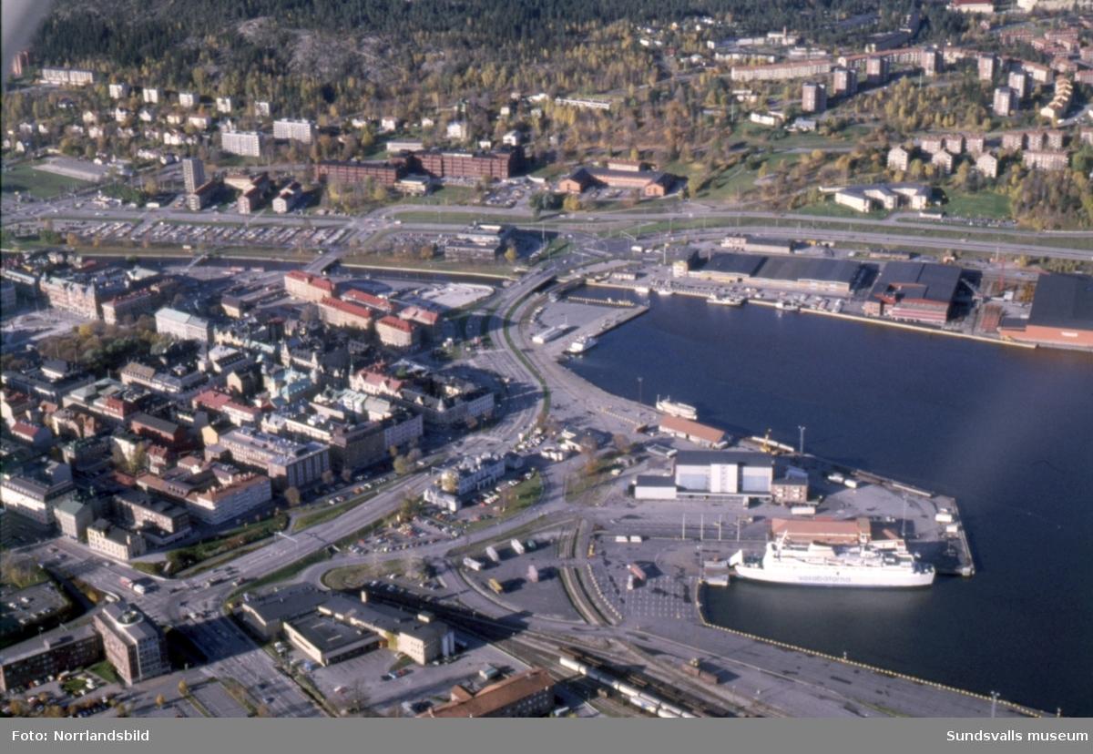 Flygfoton över Sundsvalls hamn med färjeterminalen, färjor, fryshus och omgivande bebyggelse. På den ena bilden syns att Norrmalm var en enda stor parkeringsplats innan P-huset och Teliahuset byggdes.