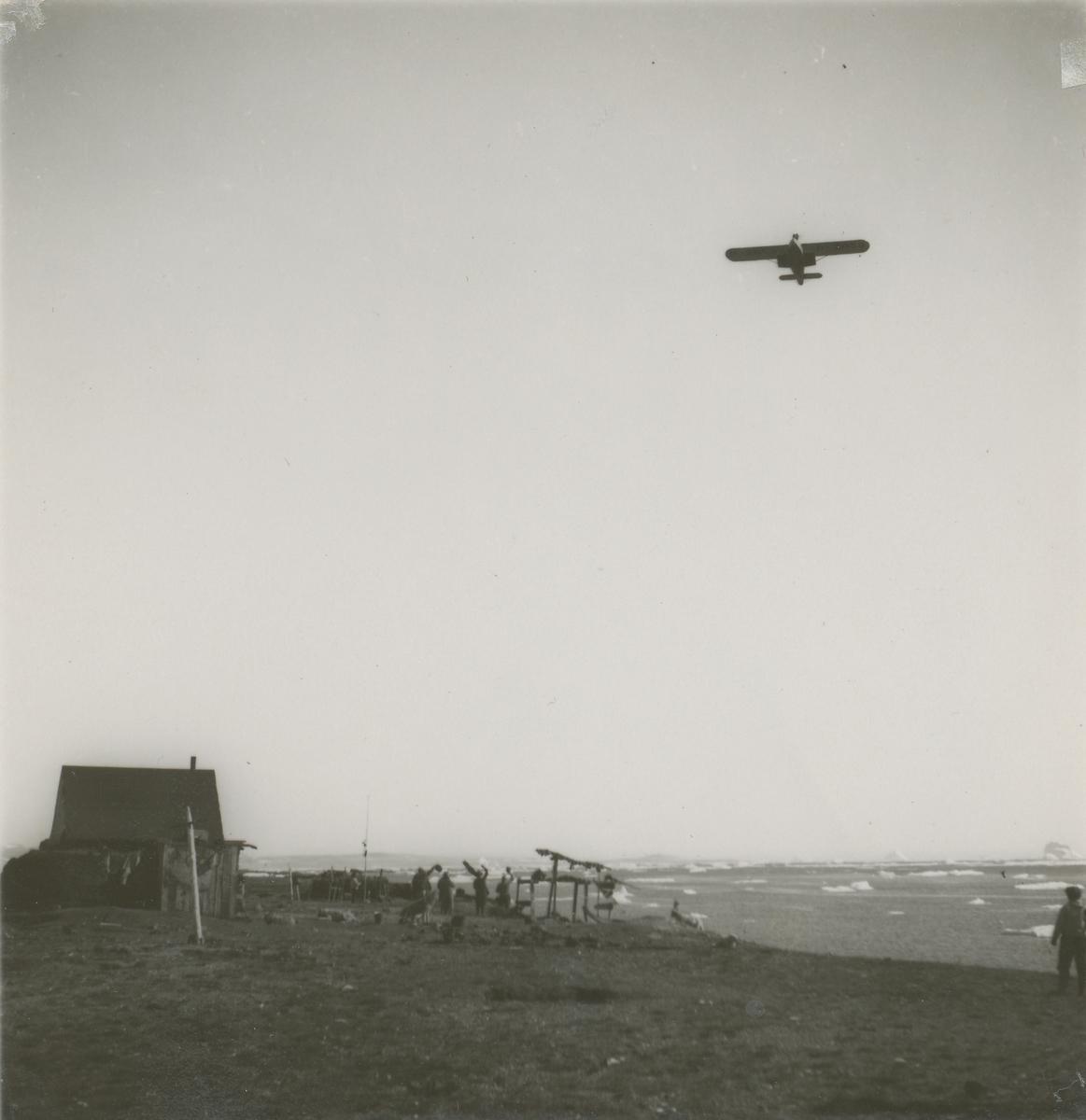 Wolfgang Von Gronau flyr over Kap Hope i Øst-Grønland. En gruppe mennesker står på bakken og vinker til flyet.