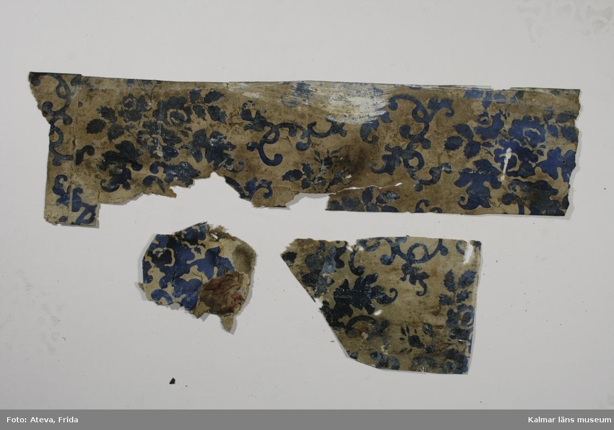 KLM 39224:1. Tapet av papper. 3 bitar. Tapeten har oblekt botten med snirkliga blomrankor i kungsblått, nyrokoko. Nytryck av tapeten, KLM 39224:10, har gjorts och sitter nu uppsatt i rummet. Datering: 1830-1870-tal, Nyrokoko.