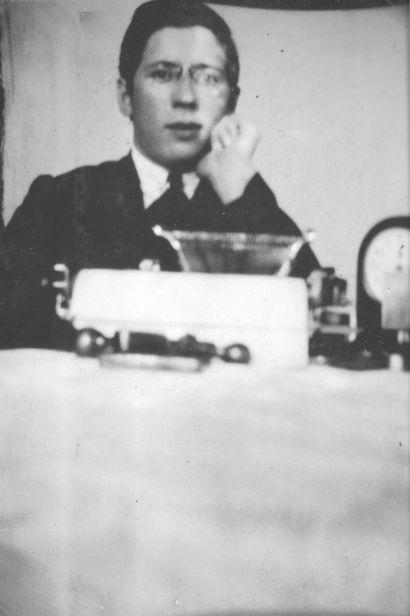 Fotografi av en ukjent, dresskledt ung mann som sitter ved et bord.
