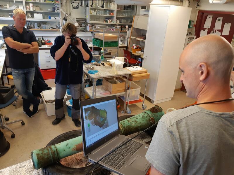 Kanon ligger polstret med bildekk på et bord i et laboratorium. En person holder en bærbar datamskin tilkoblet en håndholdt skanner og måler inn kanonen i 3D. En person fotograferer kanonen fra motsatt side. (Foto/Photo)