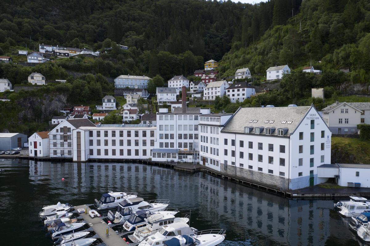 Den tidlegare tekstilfabrikken Salhus Tricotagefabrik sett frå sjøen. (Foto/Photo)