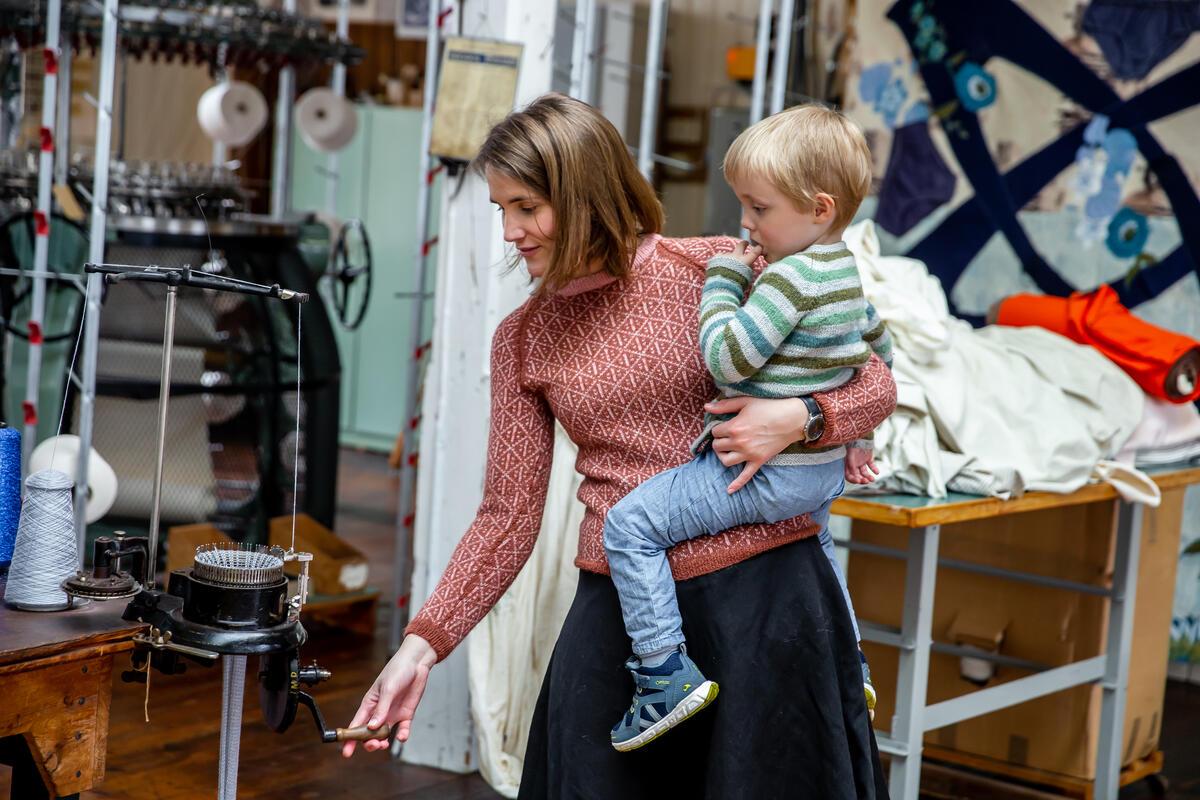 kvinne og barn med strikka gensarar sveivar på lita maskin (Foto/Photo)