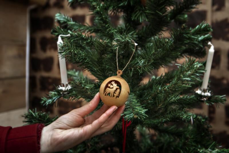 En hånd viser frem en julekule på juletreet (Foto/Photo)