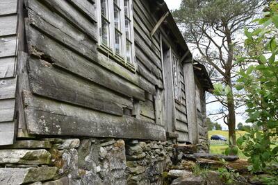 eldre trebygning med steinmur, i bakgrunnen tre og busker. Foto/Photo