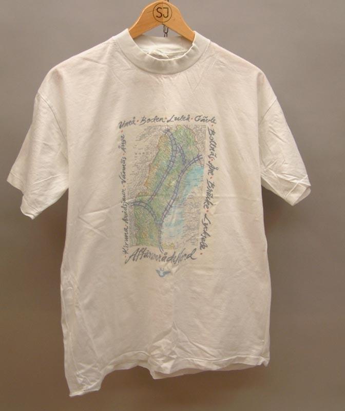 Vit t-shirt med tryck av en rektangulär järnvägskarta med stationsnamn runt sidorna. Under kartan står texten Affärsområde Nord i svart, samt en SJ-logga i blått.  Storlek L  Modell/Fabrikat/typ: Best In Town