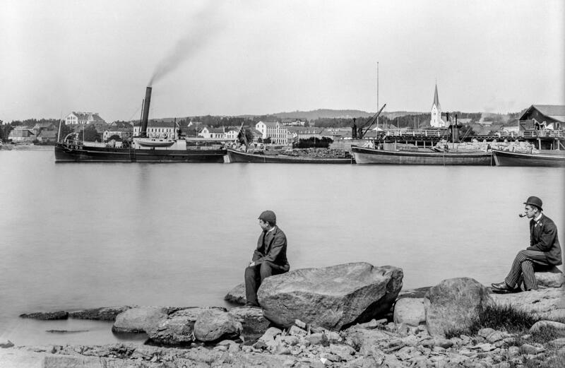 Svart-hvitt foto som viser en ung gutt og en mann med pipe som sitter på store steiner i forgrunnen. bak dem, på Mjøsa, ligger flere båter, og i bakgrunnen ser vi blant annet Hamar domkirke. (Foto/Photo)
