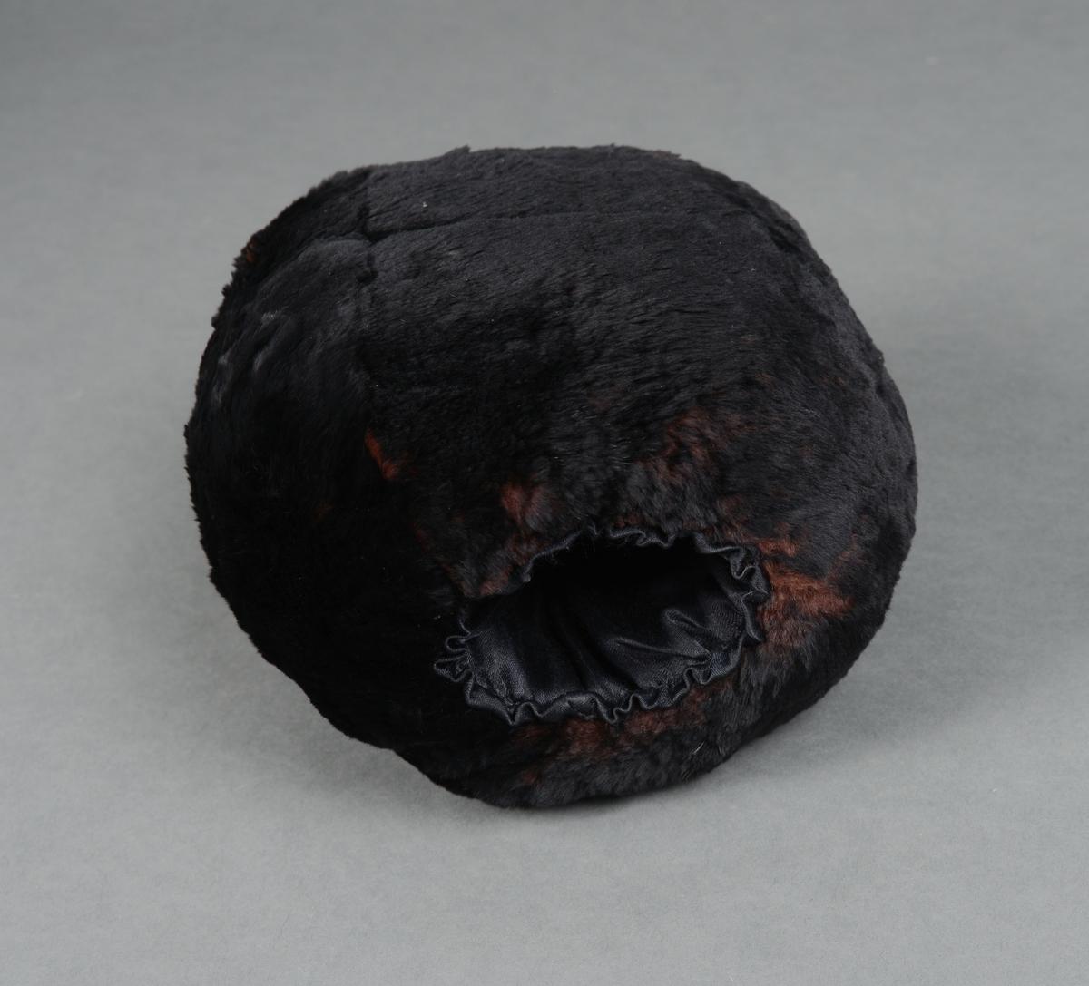 Muffe med korthåret svart pels. Sylinderformet stoppet muffe med svart silkefor. I den ene enden er det en hempe til å henge den opp etter.
