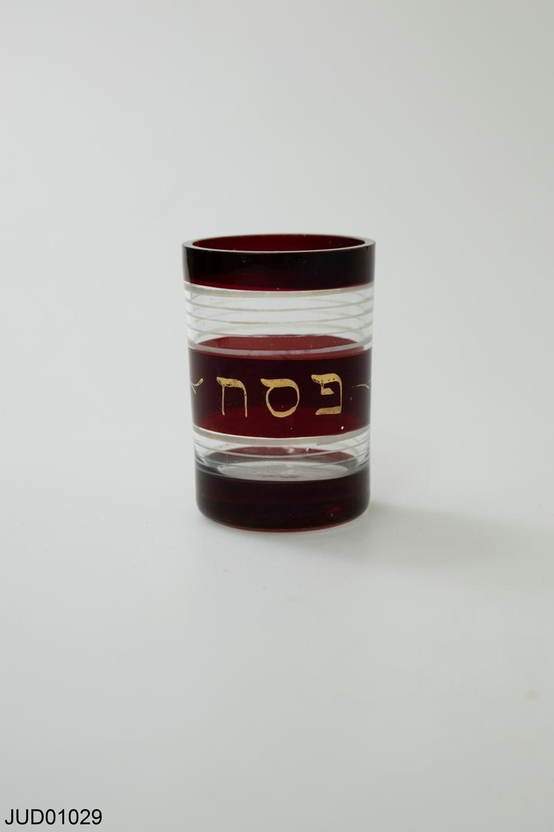 Litet glas med röd bård och text på hebreiska.