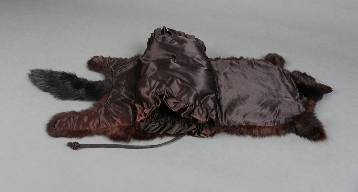 Muffe med korthåret svart pels. Sylinderformet stoppet muffe med svart silkefor. I den ene enden er det en hempe til å henge den opp etter. I begge endene er det påsydd dobbelt lag med for som er rynket sammen til en rysjkant. Lomme med stoff som er lagt i legg på utsiden av selve muffen. Pelsen er festet i overkant av muffen. Pelsen er også vattert og foret med silkestoff.