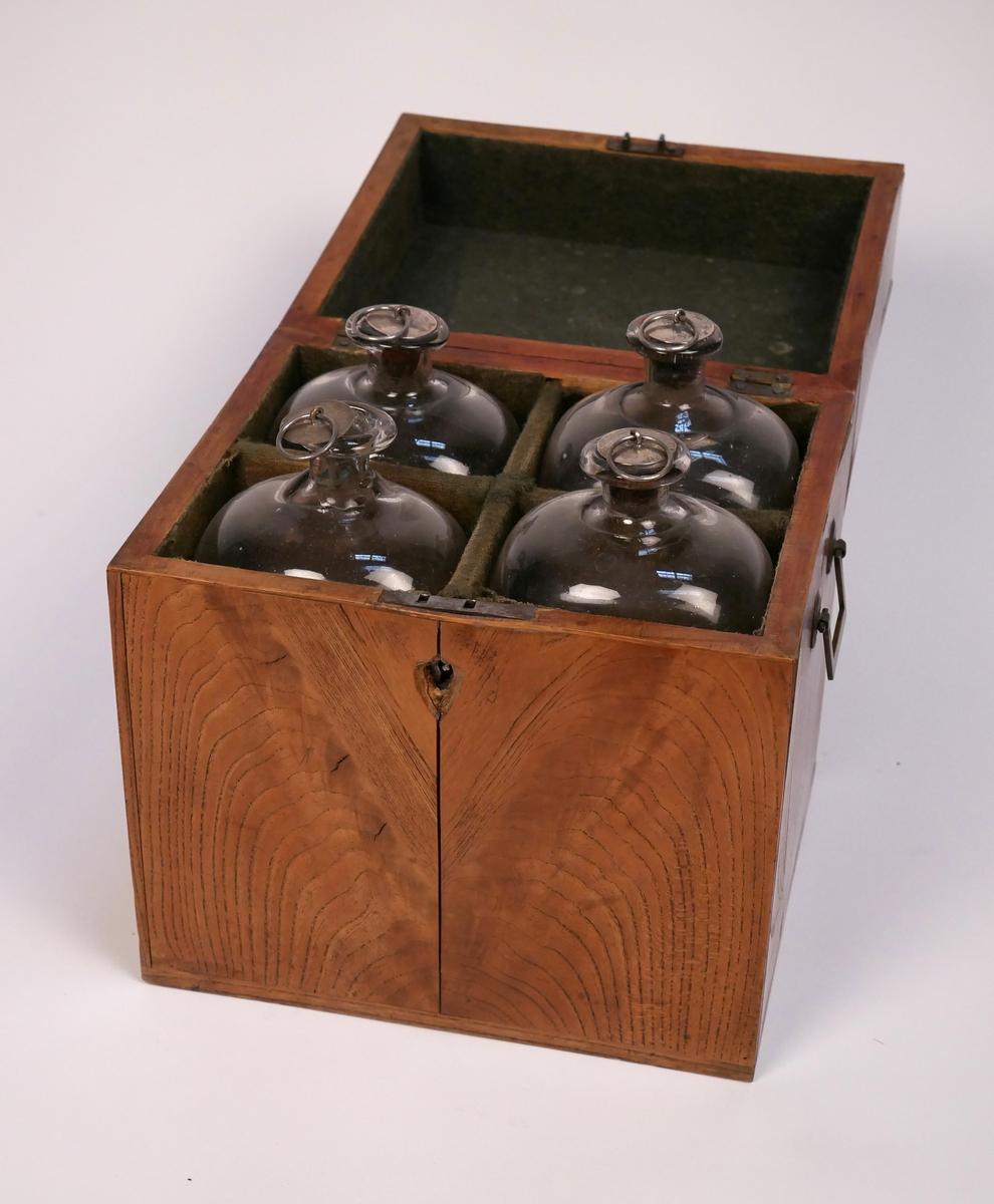 Schatull för förvaring av fyra flaskor. Tillverkat av alm med intarsia i stjärnform på locket. Flaskornas silverkorkar märkta AB = Anders Bäck, mästare i Alingsås (1828-1851)  Har varit i bruk på Bolltorp, Alingsås
