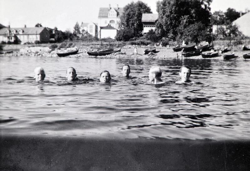 Svart-hvitt foto av seks mannshoder som stikker opp av vannet under en svømmetur. Bymiljø i bakgrunnen. Koigen, Hamar. (Foto/Photo)