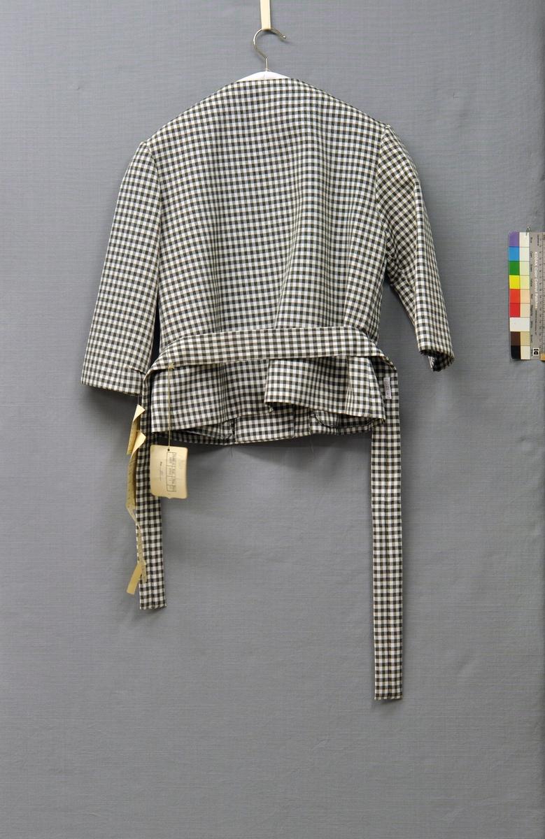 Dräkt bestående av jacka, kjol och skärp. Av viskosrips rutig i svart och vitt.  Jackan rak och höftlång. Framsidan av 2 delar med 2 bystinsnitt. Knäppt över bröstet med 2 stora pärlemorknappar och passpoalerade knapphål. Baksidan helskuren, slät. Rund ringning, 3/4-ärm. 2 låga stolpfickor i höfthöjd. 5 cm brett knytskärp.  Kjolen rak av 2 stycken. Framsidan med 8 små lagda veck i midjan. Baksidan slät med 2 gångveck och 2 midjeinsnitt. 3 cm bred linning. Fodrad med ljusgrå viskostaft. Knäppt med gråbrun herrknapp och blixtlås i vänster sida. Storlek 40.