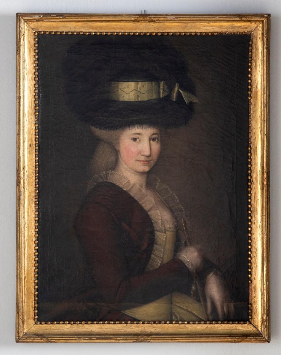 Kvinneportrett, malt på lerrett. Kvinne iført mørk jakke samt fjærhatt, fremstilt i trefjerdedelsprofil. Hun holder en ridepisk i høyre hånd. Forgylt profilert treramme med perlestav.