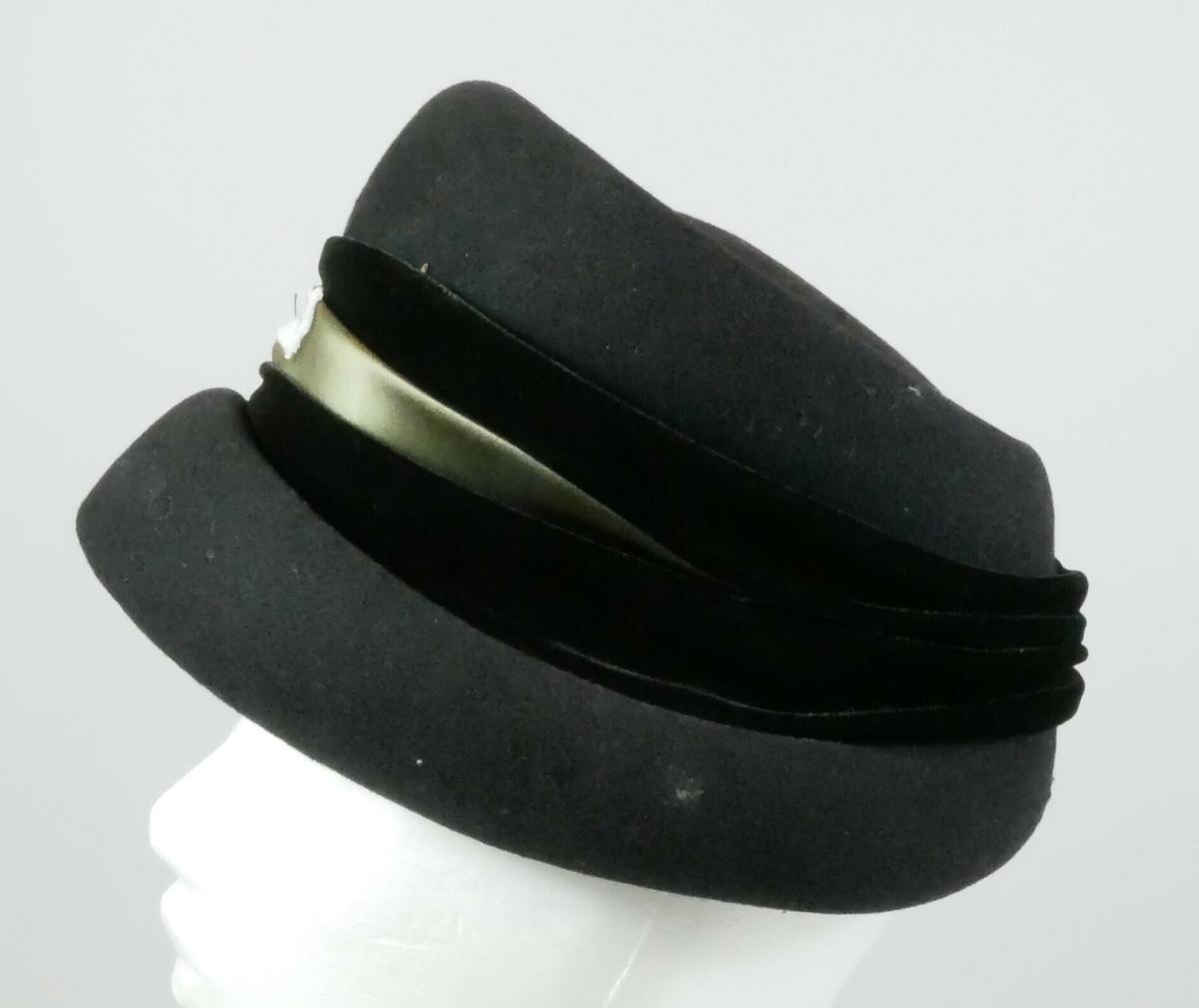 Svart hatt med fløyelsband og silkeband rundt.