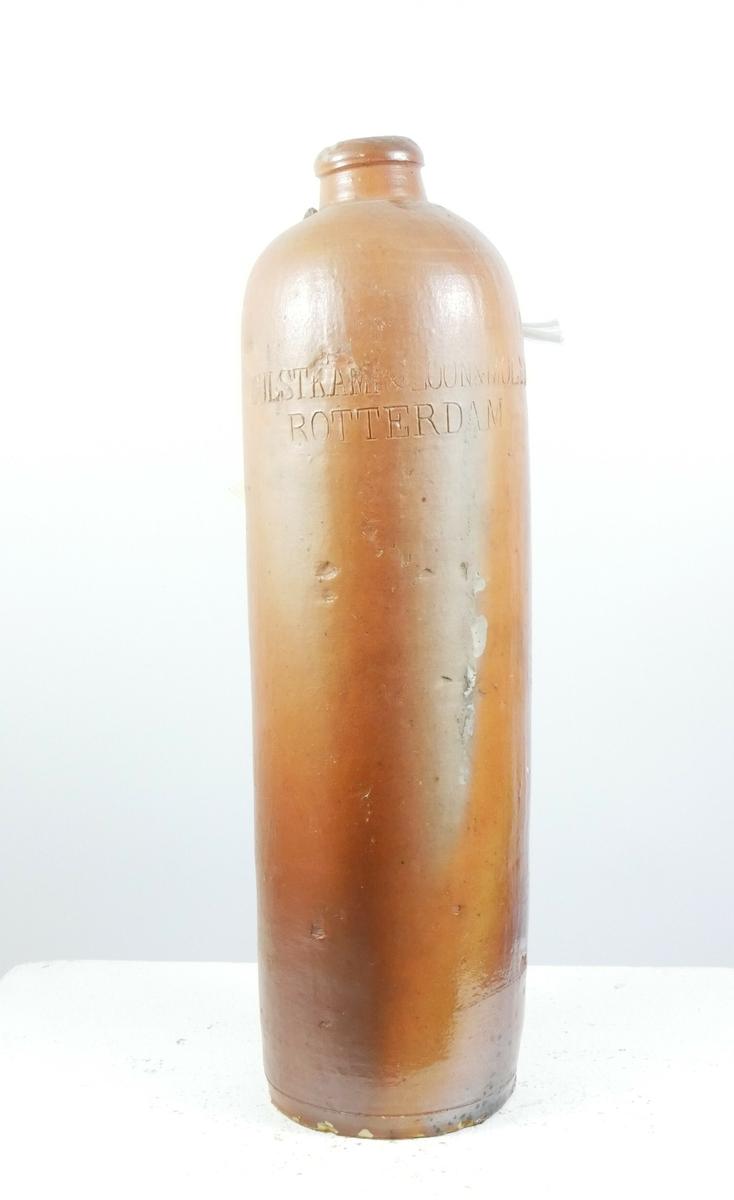 Brun sylinderformet leirkrukke til brennevin. Flasken smalner øverst og ender i en tut. På baksiden har det vært en hank.