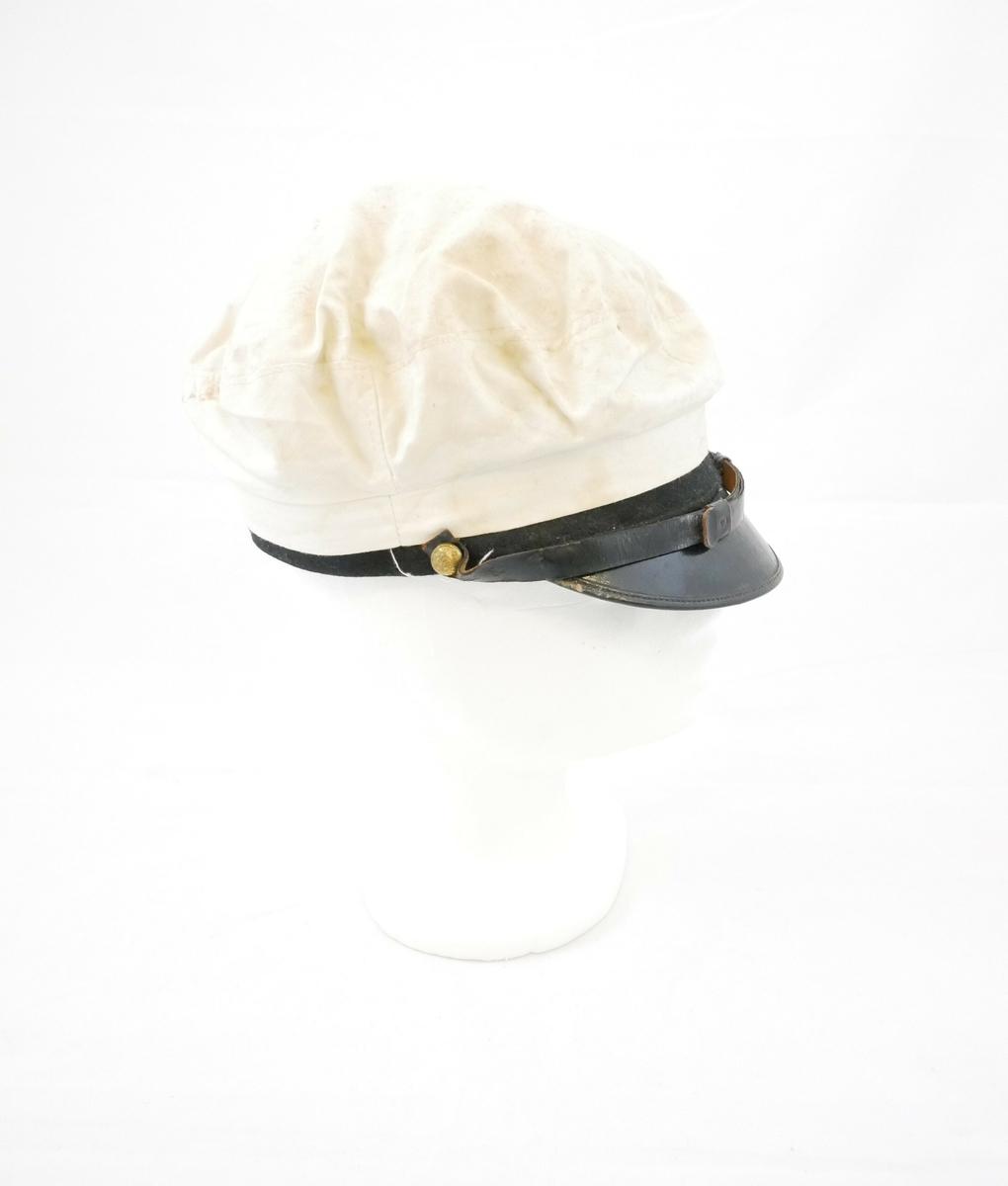 Lue med pull i hvitt bomullsmateriale, en svart brem foran på lua. Ett svart bånbd festet med to knapper i gullfarge på hver side går over bremmen.   Merkelapp, innsiden:  C BRANDT // BERGEN // NORW.