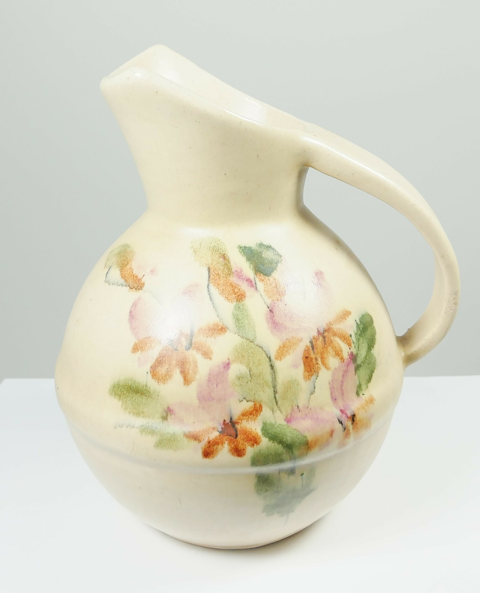 Rund hvit mugge med hank og blomstermotiv