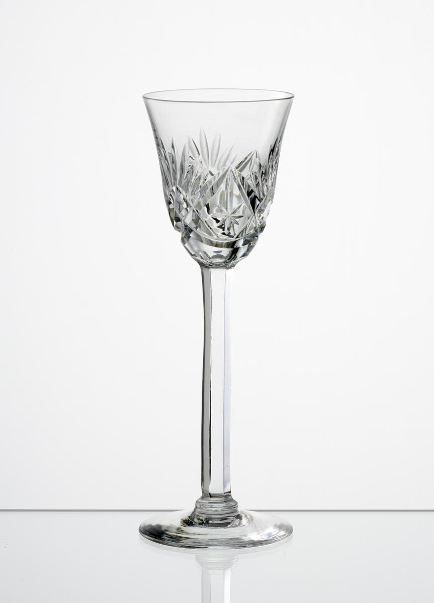Design: Okänd.  Brännvinsglas, svagt klockformad kupa med skärslipad dekor. Högt fasettslipat ben med slät fot.