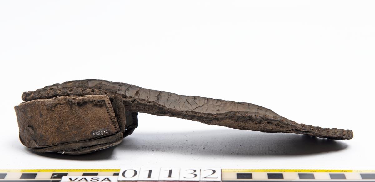 Fem delar av en recent sko. Sula fyndnummer 01132 har hål efter skopligg och kvarsittande tråd. Sulan är mycket kraftig och välbevarad. Del av sula, fyndnummer 01123:1, har hål efter skopligg och stygn runt om. Lädret är mycket kraftigt och välbevarat. En bakkappa fyndnummer 01132:2. På narvsidans mitt samt i nedre kanten finns hål efter stygn. Lädret är mycket kraftigt och välbevarat. En träklack fyndnummer 01132:3. Klackens kanter omsluts av ett tunt och spaltat lager av läder. Vid den klackkant som är vänd mot hålfoten sitter en kraftig, rektangulär läderbit fästad. På klackens undersida är förstärkt med en kraftig läderbit. Under denna sitter en laglapp. Klacken har kvarsittande träpligg. En ospecificerad, rektangulär läderbit, fyndnummer 01123:4. Längs med ytterkanterna löper hål. Lädret är kraftigt, narvsidan är dock något spaltad.