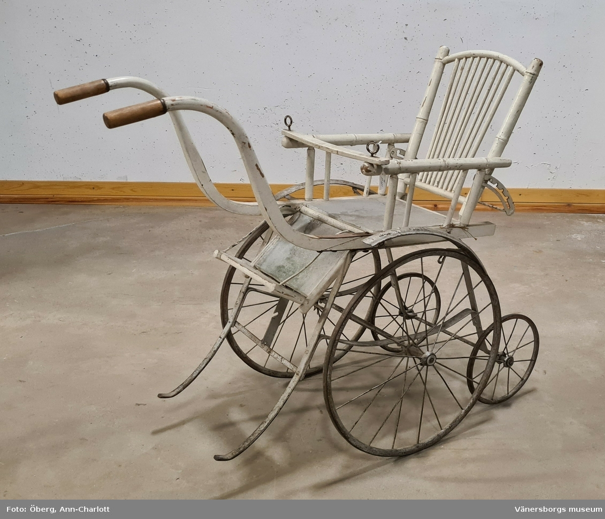 Barnvagn, sittvagn, sittkärra i trä. Kärran har två handtag. Större hjul fram och mindre hjul baktill. Ryggen är reglerbar.