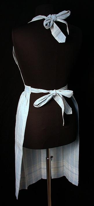Handsytt hängsleförkläde med bröstlapp i gråblått bårdvävt bomullstyg med dubbla vita ränder. Förklädet rynkat mot linning. Knytband fästade vid linningen. 2 st bågformade utanpåfickor med öppning i sidan, rundade mot förklädets ytterkant. Knytband fästade på bröstlappen för knytning runt halsen.