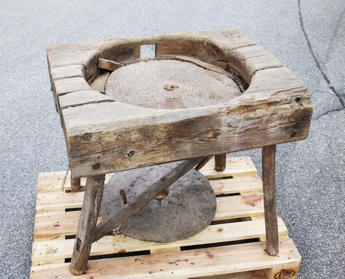 Handkvarn på fyrbent träställ. I mitten, närmast rund, infälld, platt understen. Överstenen rund, lös och konkav, med stort hål i mitten, för påfyllning av säd, samt på kanten, infällt trähandtag för att veva runt.