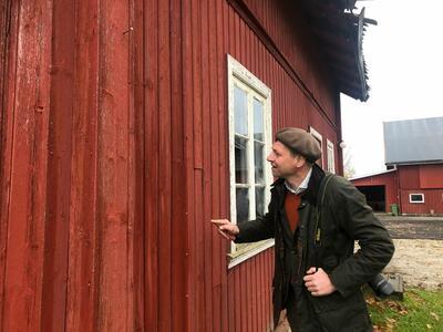 Bygningsvernkonsulent_ser_pa_rdt_hus.jpg. Foto/Photo