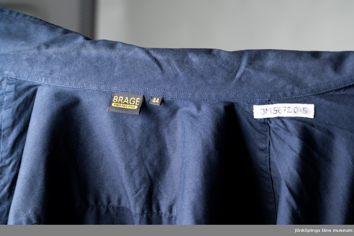 """Skjorta till stationsuniform för personal vid Räddningstjänsten i Jönköpings kommun. Långärmad skjorta av mörkblått bomullstyg. Rak modell, fast krage, ok av dubbelt tyg på ryggen och två bröstfickor med lock och knäppning med svart plastknapp. Över vänstra fickan sitter en mörkblå tygetikett med gul text: """"Brandmästare Jan Green"""". På vänster arm vid axel sitter ett tygmärke med text: """"RÄDDNINSTJÄNSTEN JÖNKÖPINGS KOMMUN"""" runt bild av Jönköpings stadsvapen. Knäppning fram med sju svarta plastknappar, manschetter med två svarta plastknappar och en svart plastknapp i ärmsprundet samt två reservknappar på insidan. Tygetikett i nacken: """"BRAGE PROTECTIVE"""". Etikett med produktinformation på insidan. Storlek 44.  Samhör med: JM 56720:1-7.  Se vidare Historik."""