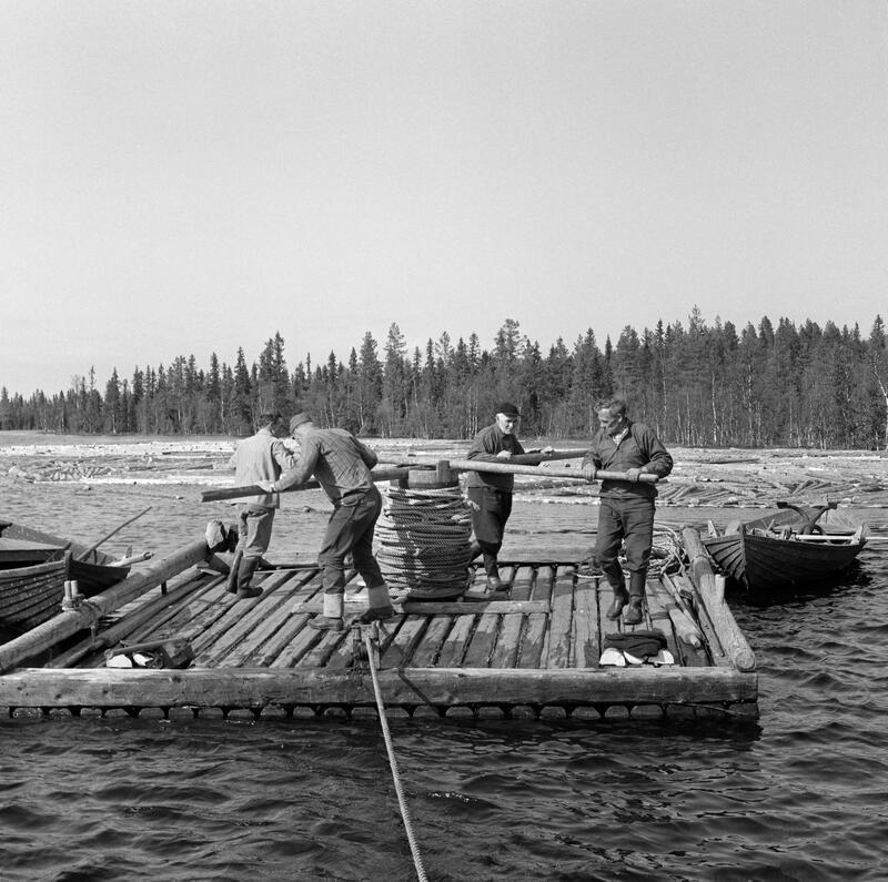 Foto av tømmerflåte med manuell vinsj som betjenes av fire personer. (Foto/Photo)