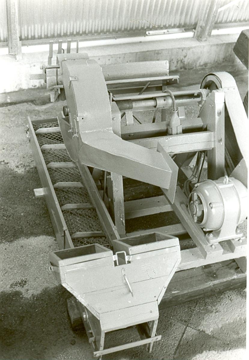 Gråmålad vedkap, eldriven. Kapen står på trästativ, och är av järn, med transportör i trä med transportband av stålnät. Kaptrissan drivs med kilrem från elmotorn, 7,5 hkr, 380 V, 2880 varv.  Typ: GK B3 Nr: 2649 Motor: Siemens Schuckert, nr 823952