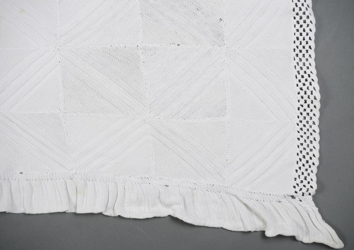 Sengeteppe strikket i hvit bomull. Teppe er sydd sammen av 165 ruter. De 2 langsidene har påsydd en strikket rillekant som er brettet inn mot baksiden og sydd til for hånd. Kortsidene har påheklet kant som dekor.