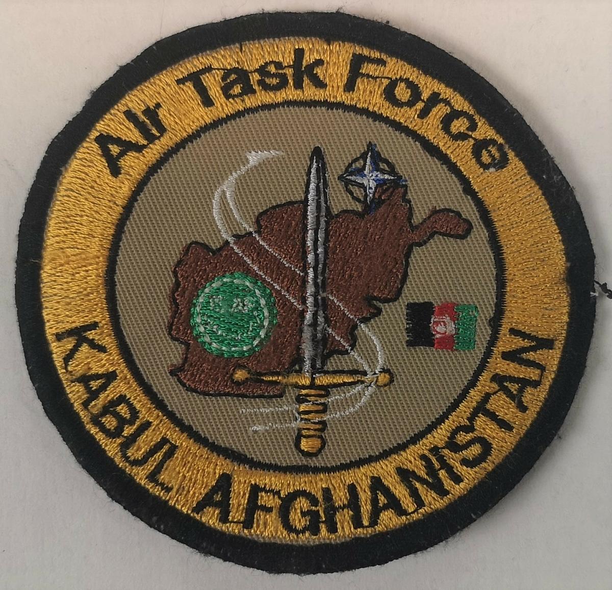 NATO og ISAF logo i sentrum, over kartutsnitt av Afghanistan.