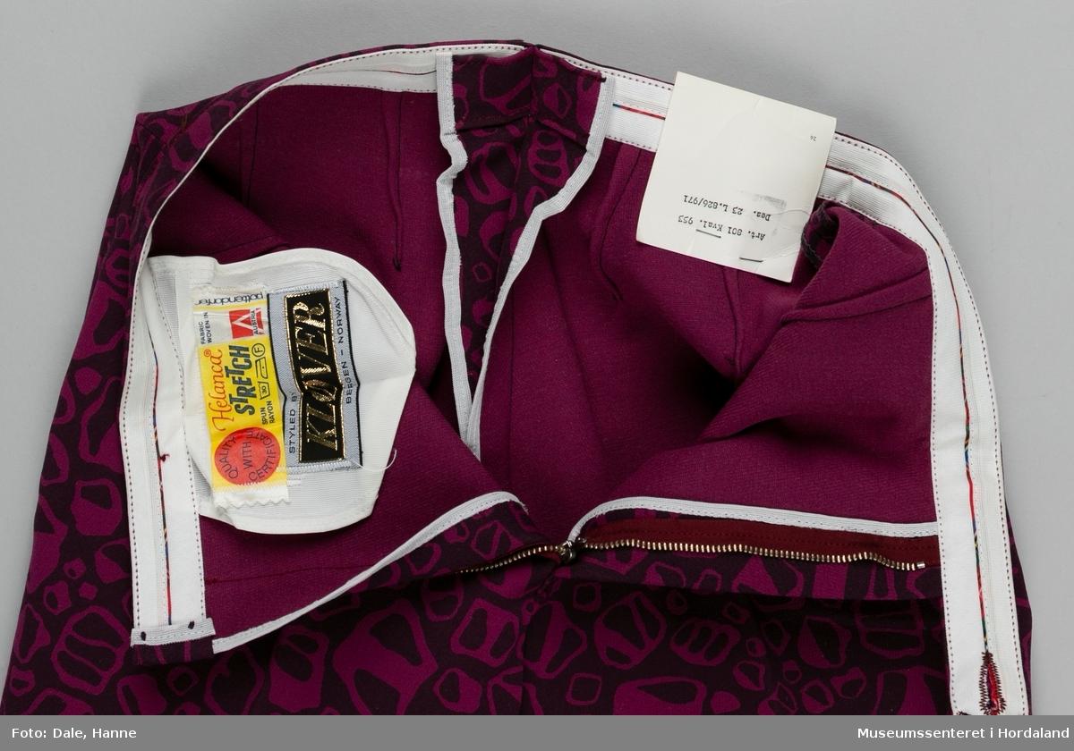 """Mønstrete mørk rosa bukse med press, knappelukking og glidelås frå Kløver. Forsterkande band på innsida av bukselinninga. fôr frå kneet og ned med påsydd strikk under foten. Str. 40. Den er sydd i eit blandingsstoff. Frå merkelappen: """"Stoffet er 55 % HELANCA/NYLON og 45 % ULL, med god elastisitet. Behagelig i bruk. Holder pressen. Kan vaskes (finvask 35 grader) og renses."""""""