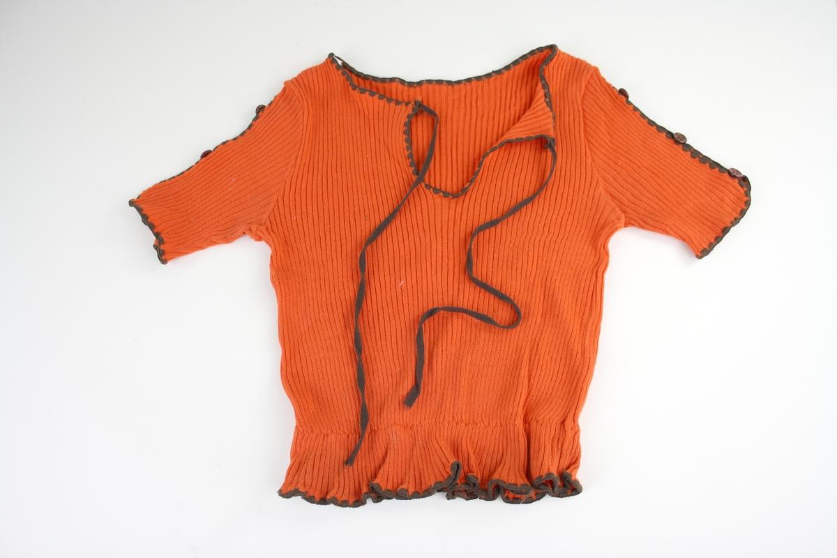 Kortärmad orange tröja. Tröjan har en snörning i urringningen och en resår som bildar en volang vid midjan. Ärmarna har en slits som är ihopfästad med tre bruna knappar. Halslinning, snören samt kanterna är bruna.  Tillverkad av Fix i storlek 150.