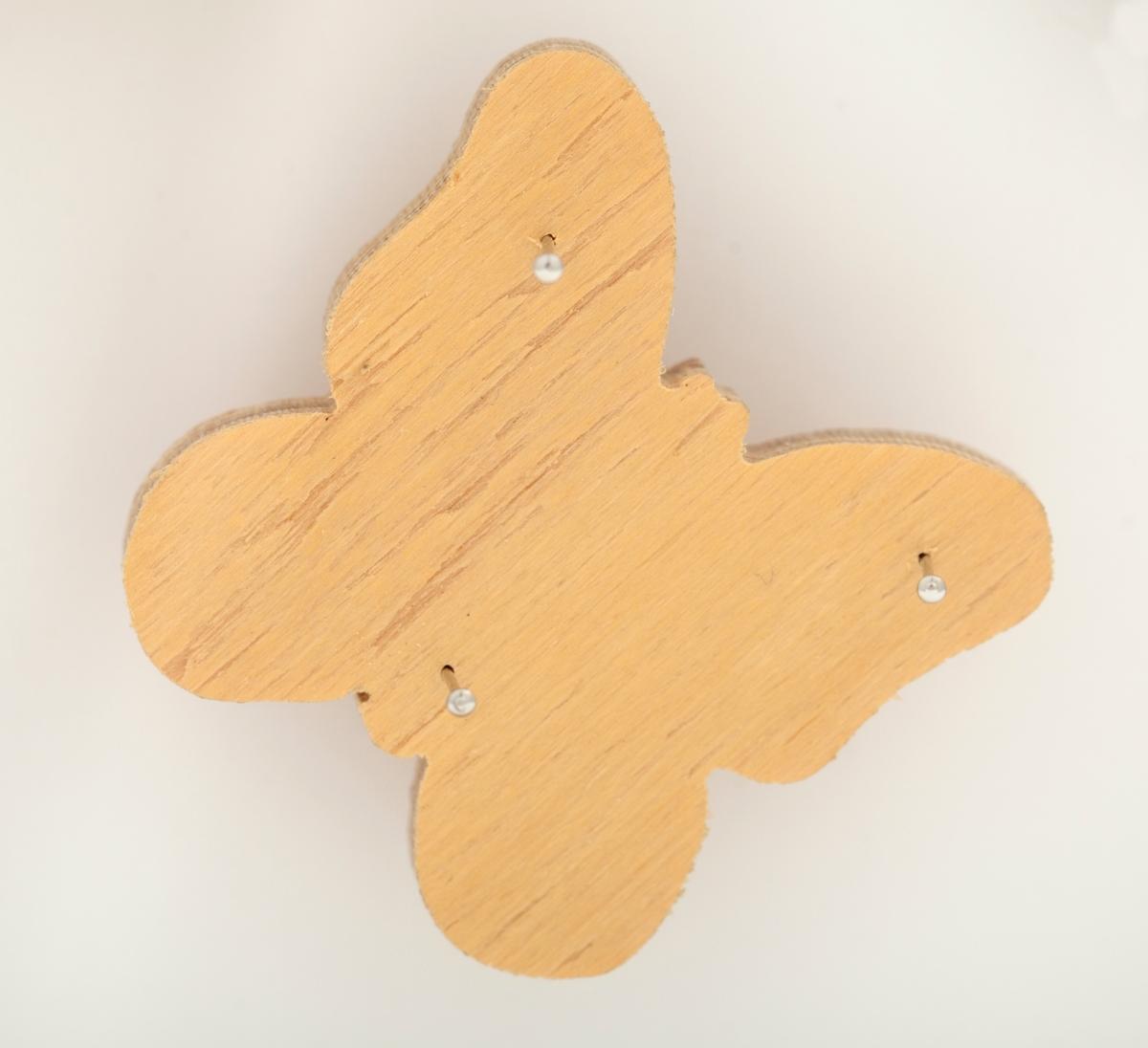 """Åtte """"samlerobjekt"""" utformet i tre.  Del av veggobjekt.   En rektangulær, avlang treplate med et geometrisk mønster som ligner et åkle. Mønsteret er brodert med svart tråd gjennom små perforeringer i treplaten.   Et ovalt miniatyrbilde med gullramme og et brodert tempel i blå-nyanser.  Seks sommerfugler med samme form, men ulik utforming:  To hvitmalte sommerfugler med broderier i henholdsvis lys gul-oransje tråd og rød og rosa tråder.  To trefargede sommerfugler med broderier i henholdvis beige tråd og svart tråd.  To trefargede sommerfugler uten broderier."""