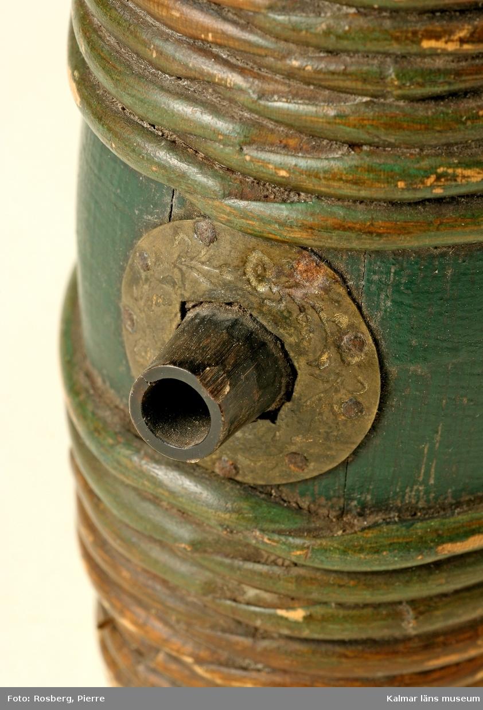 KLM 5590. Brännvinskärl. Form av en bandad laggad tunna med smalt oval genomskärning, tätt lagda vidjeband. I sprundet en kort pip av horn, runt pipen mässingsbeslag dekorerat med blommor och blad. Grönmålad med röda bottnar i dessa med vitt: Anders -- Hobro 1867.