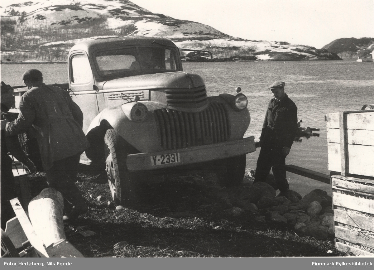 """En lastebil og noen brubjelker ble losset fra D/S """"Slettnes"""" på en flåte for å frakte det til land, Ifjord-Lebesby 1946. Her kjører lastebilen fra flåten, opp på land. Tre menn, oppsynsmann Johannes Foslund til høyre, ser til at alt går etter planen. Lastebilen y-2331, eier Gustav Simonsen, ble hentet i Smalfjord."""