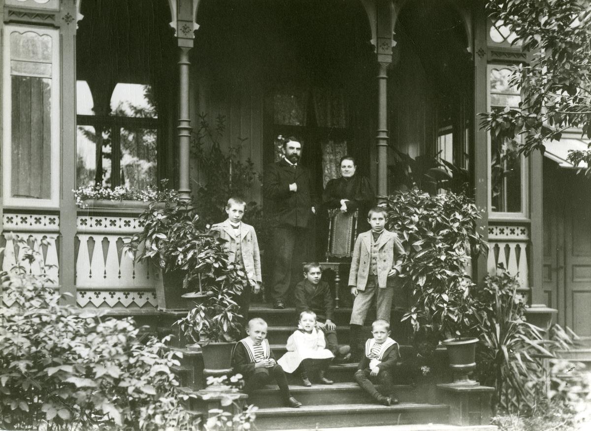 "Glacis gate 7, Fredrikstad. Anthon B. Nilsens hus. Øverst: Anthon B(ernhard Elias) Nilsen (1855-1936), ""Elias Kræmmer"", og Gurine Helene Nilsen. f. Holst (1861-1939). Sittende sønnene Bernhard, Ingar og Joar, Nederst barna Reidar, Tordis og Gunnar."