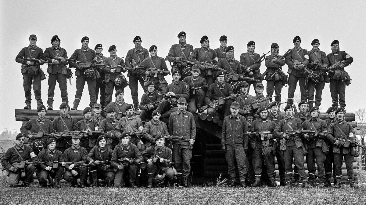 Pionjärarbetsplatsen, 2 april 1986   Pionjärplutonen 1985-86. Bild 1 och 2.  Plutonen på en arbetsmodell av ett truppskyddsrum. I mitten står plutonchefen, kapten Per (Pysch) Andersson och stf, löjtnant Hans Hedenskog. Bild 3 till 5.  Pionjärgrupper Bild 6.  Bromaterielgrupp.  Milregnr: 331145, 331216